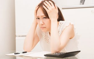 机で頭を抱え悩む女性