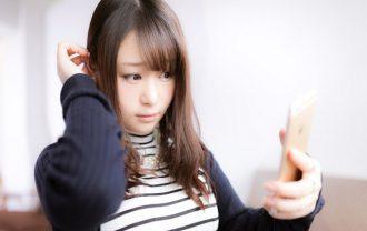 鏡で白髪を確認する女性