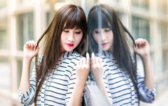 鏡をみて髪を触る女性