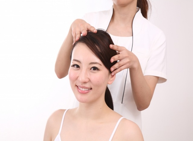 頭皮をマッサージされる女性